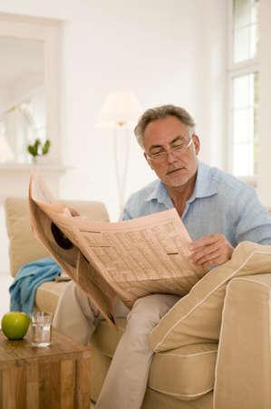 early fifties: Mature man reading newspaper on sofa