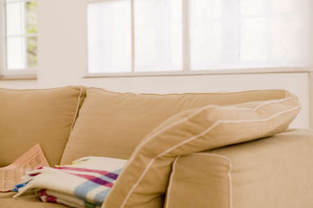 differential focus: Blanket and newspaper on sofa,close-up