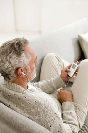 oap: Mature man listening to MP3 player,close-up,elevated view LANG_EVOIMAGES