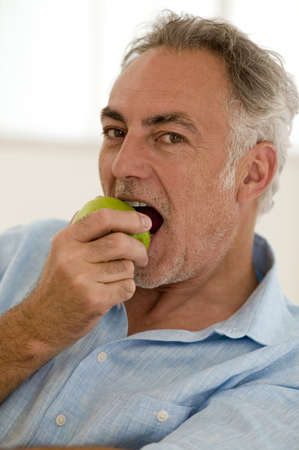 grizzled: Mature man sitting on sofa eating apple,portrait