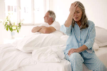 disappoint: Mature couple sitting on bed (focus on woman in foreground with head in hands) LANG_EVOIMAGES