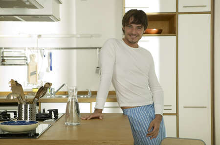 gratify: Young man standing in kitchen,smiling,portrait LANG_EVOIMAGES