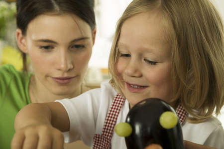 confiding: Mother playing with daughter in kitchen