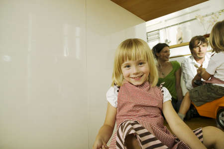 confiding: Little girl in kitchen,portrait,parents in background