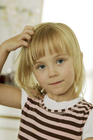 kind hearted: Girl (2-4) with hand in hair,portrait