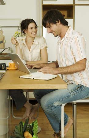 trabajando en casa: Joven pareja en la cocina, el hombre usando la computadora port�til, sonriendo LANG_EVOIMAGES
