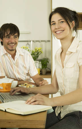 confiding: Young couple in kitchen,woman using laptop,smiling LANG_EVOIMAGES