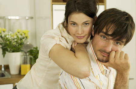 embracement: Young couple in kitchen,close-up,portrait