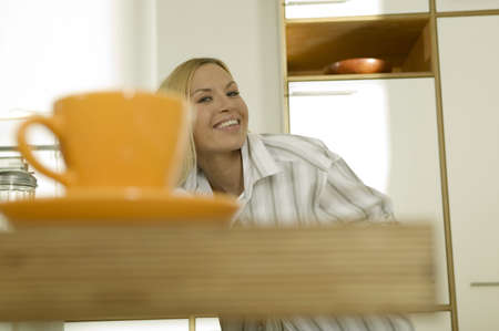hope indoors luck: Woman sitting in kitchen,smiling,(focus on background)