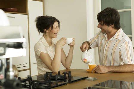 diverted: Young couple in kitchen,drinking tea,smiling LANG_EVOIMAGES