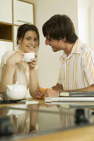 confiding: Young couple drinking tea in kitchen,smiling,portrait LANG_EVOIMAGES