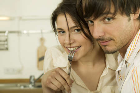 hope indoors luck: Young couple in kitchen,woman holding fork,portrait