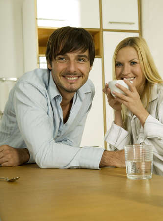 confiding: Young couple in kitchen,woman holding coffee cup,smiling