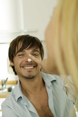 confiding: Young woman pointing nose of man,close-up