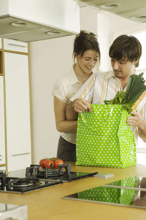 shoppingbag: Young couple in kitchen,looking in shopping bag