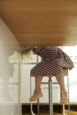 directly below: Girl (2-4) peeking under table,sitting in kitchen