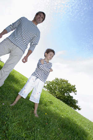 confiding: Father and son (4-7) standing in park, low angle view LANG_EVOIMAGES