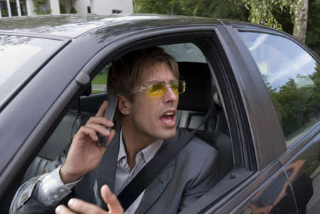 infuriate: Businessman using mobile phone in car, shouting, close-up