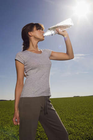 quarter horse: Young woman drinking from water bottle