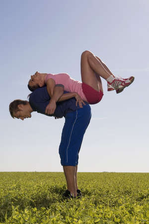 stemming: Young couple exerting gymnastic on meadow, side view LANG_EVOIMAGES