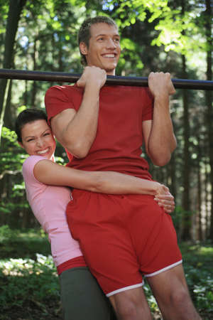 embracement: Young couple exercising on horizontal bar, smiling