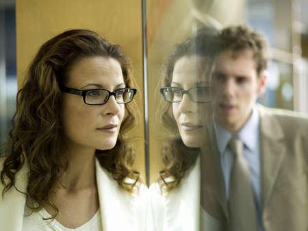dissension: Businesswoman and businessman, man standing behind window pane