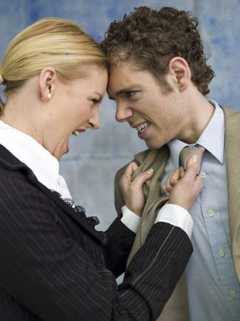 dissension: Businesswoman grabbing man by tie, shouting, side view, close-up LANG_EVOIMAGES
