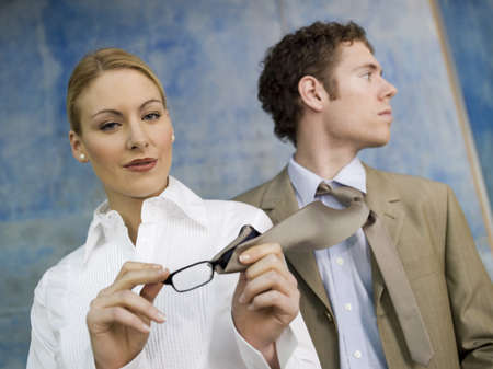 superiority: Business woman cleaning spectacles with man´s tie LANG_EVOIMAGES