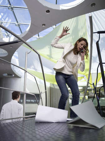 falling out: Young businesswoman using mobile phone, papers falling on floor