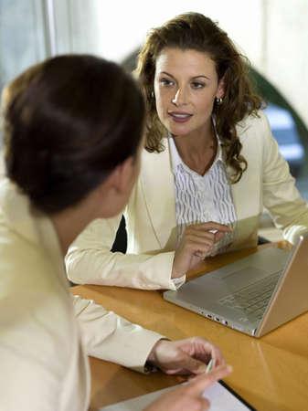 technology: Businesswomen sitting at desk with laptop