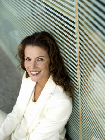 pantsuit: Businesswoman sitting on floor, smiling, elevated view, portrait