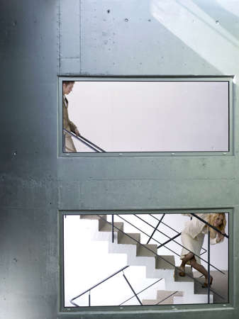 gratify: Businessman and woman on staircase, woman peeking LANG_EVOIMAGES