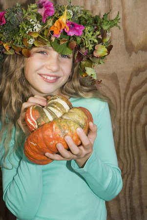 gratify: Girl (7-9) wearing wreath of flowers, holding pumpkin, portrait, close-up LANG_EVOIMAGES