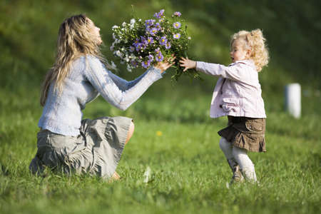 kind hearted: Daughter giving mother bunch of flowers, side view LANG_EVOIMAGES