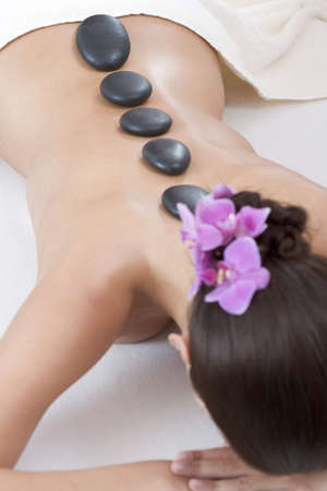 Young woman receiving hot stone massage, rear view Stock Photo - 23708103