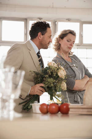 confiding: Mature couple in kitchen with flower bouquet