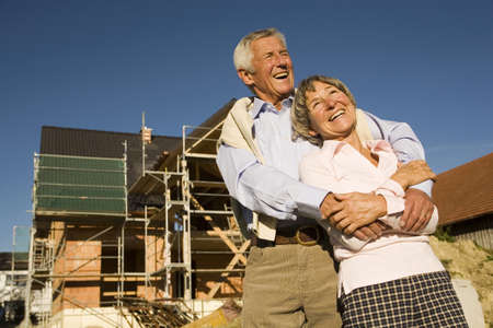 looking away from camera: Senior couple embracing in front of construction site, laughing, low angle view