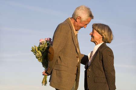 oap: Senior couple, man hiding bouquet, smiling, side view