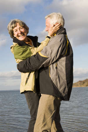embracement: Senior couple embracing, smiling LANG_EVOIMAGES