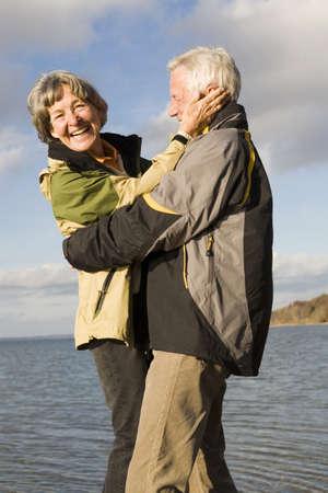 gratify: Senior couple embracing, smiling LANG_EVOIMAGES