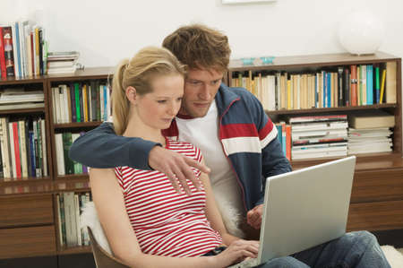 embracement: Young couple sitting on chair, using laptop