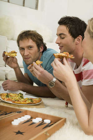 backgammon: Three young people lying on floor, eating pizza