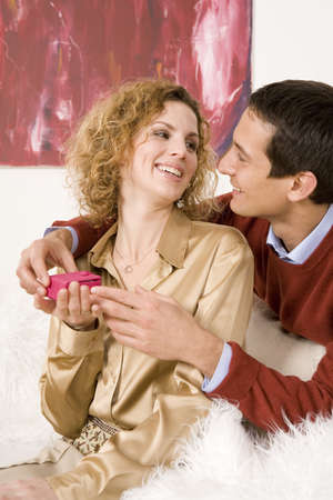 confiding: Man giving Christmas present to woman, smiling, close-up LANG_EVOIMAGES