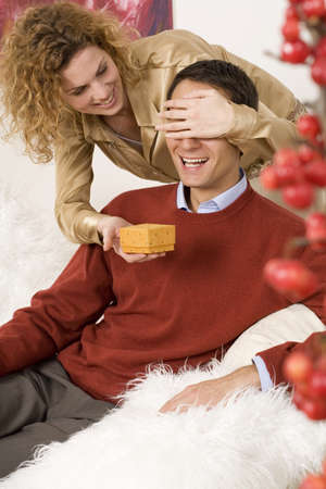 mirthful: Woman covering eyes of man, giving Christmas present