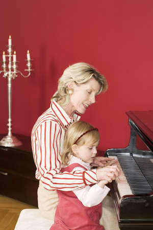 grand daughter: Grand mother and grand daughter (3-5) sitting at piano, side view
