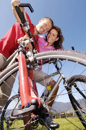 scenaries: Young couple on bicycle, smiling, low angle view, portrait