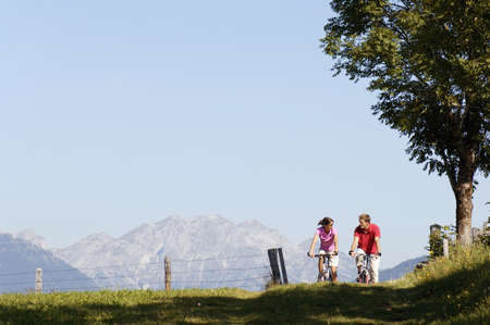 scenaries: Young couple riding mountain bike, face to face