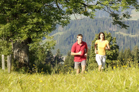 non moving activity: Young couple jogging in meadow, mountains in background