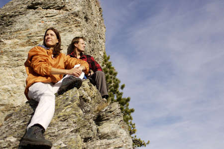 scenaries: Young couple relaxing on mountain peak, low angle view LANG_EVOIMAGES