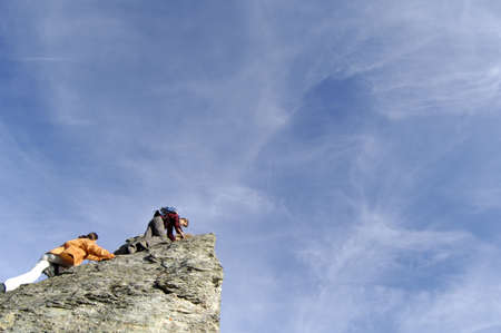 scenaries: Young couple climbing on mountain peak, low angle view